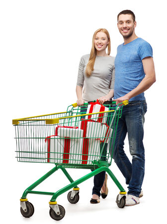 smiling couple with shopping cart and gift boxes in it photo
