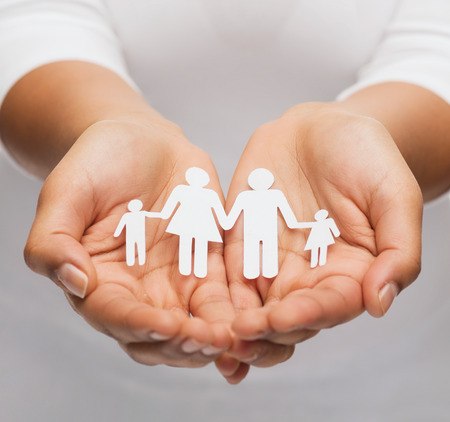 protect family: closeup of woman cupped hands showing paper man family