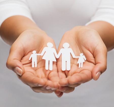 planificacion familiar: primer plano de la mujer las manos ahuecadas mostrando el hombre de papel de la familia