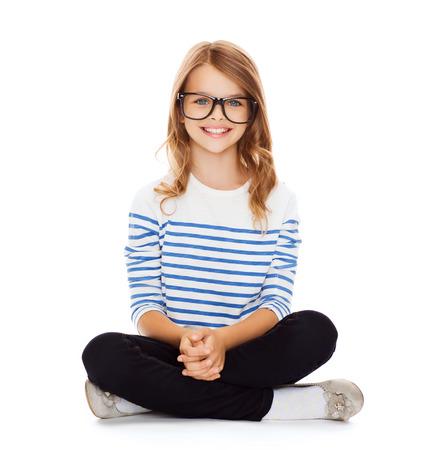 smiling girl in eyeglasses sitting on floor Stock Photo