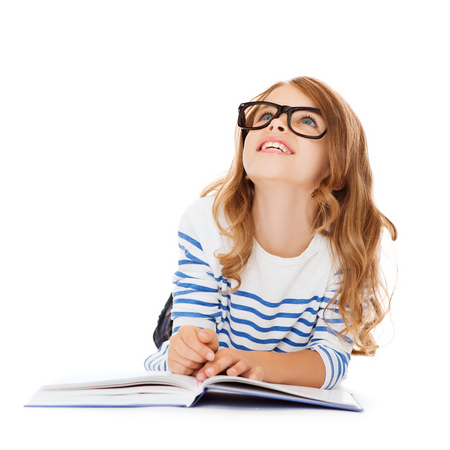 smiling little student girl with book and eyeglasses lying on the floor and looking up