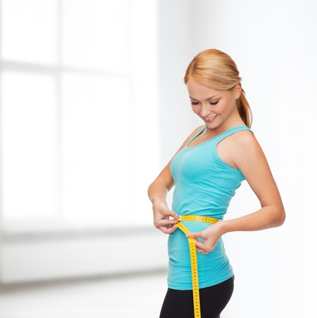 woman measuring: diet, sport and heath concept - beautiful sporty woman with measuring tape