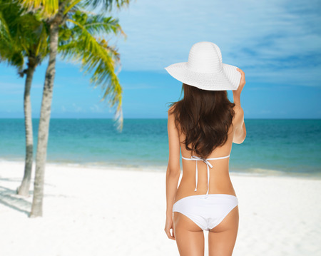 hair back: summer and holidays concept - woman posing in white bikini with hat