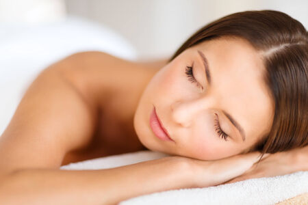 beauty eyes: beauty and spa concept - beautiful woman with closed eyes in spa salon lying on the massage desk
