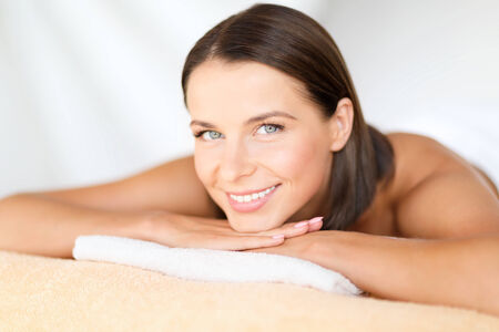 health, beauty, resort and relaxation concept - beautiful woman in spa salon lying on the massage desk photo