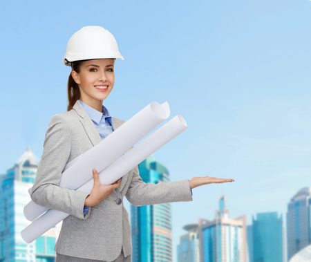 developing: building, developing, consrtuction and architecture concept - smiling architect in helmet with blueprints showing something on palm of hand