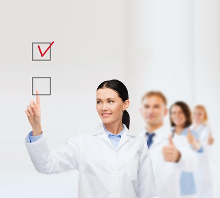 smiling female doctor pointing to checkbox