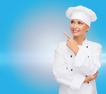 cooking, advertisement and food concept - smiling female chef, cook or baker pointing finger to something photo