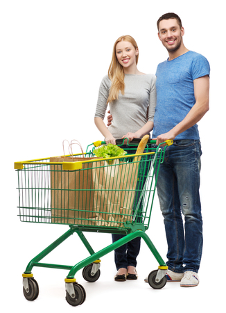 smiling couple with shopping cart and food in it photo
