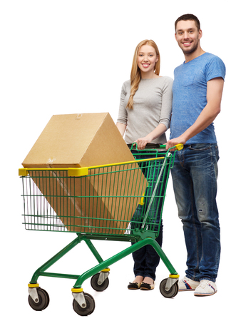 shopping trolley: happiness,electronics, shopping and couple concept - smiling couple with shopping cart and big cardboard box in it