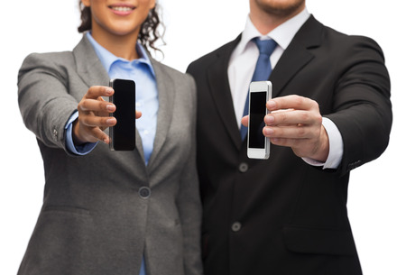 business, technology, internet and office concept - businessman and businesswoman with blank black smartphone screens in office photo