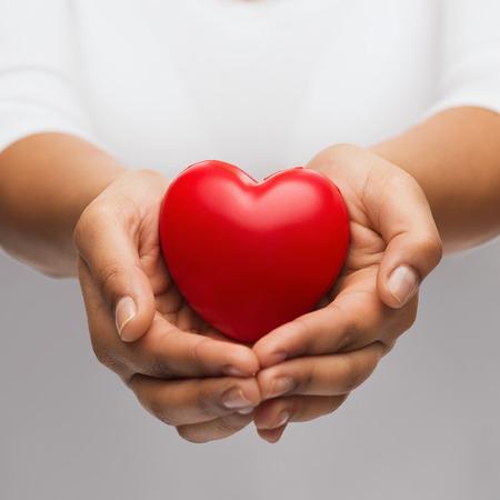 Menschen, Beziehung und Liebe Konzept - Nahaufnahme von womans hohlen Händen, das rote Herz