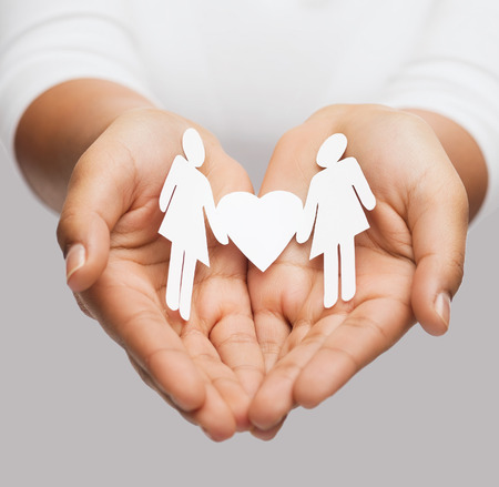 love and relationships concept - womans hands showing two paper women with heart shape photo