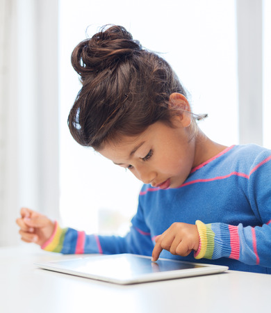 education, technology and internet concept - little girl with tablet pc Stock Photo