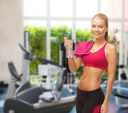 fitness and gym concept - sporty woman with bottle of water at gym photo