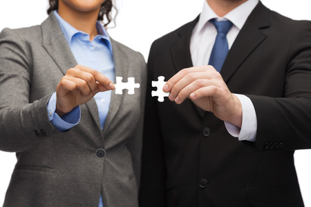 two piece: business concept - businessman and businesswoman trying to connect puzzle pieces in office Stock Photo