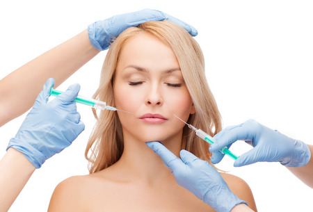 woman with closed eyes and beautician hands with syringes photo
