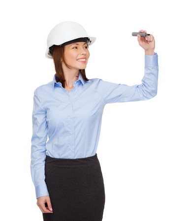 building, developing, consrtuction and architecture concept - smiling businesswoman in white helmet writing something on virtual screen photo
