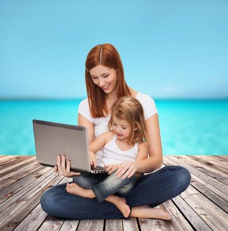 jugando videojuegos: madre feliz con adorable niña con ordenador portátil