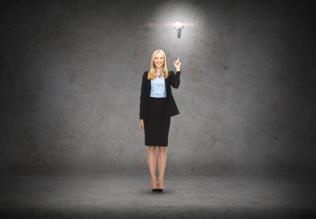 business and education concept - attractive young businesswoman with her finger up and light bulb photo