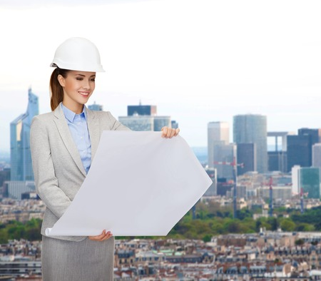 developing: building, developing, consrtuction and architecture concept - friendly young smiling architect in white helmet with blueprints Stock Photo