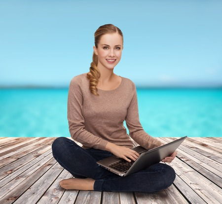 happiness, internet, technology and people concept - smiling young woman sitting on floor with laptop computer photo