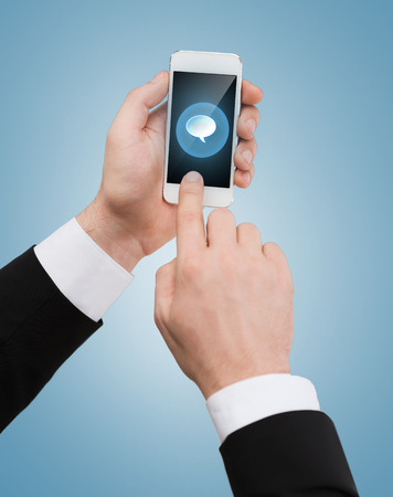 business, internet and technology concept - businessman touching screen of smartphone with text bubble photo