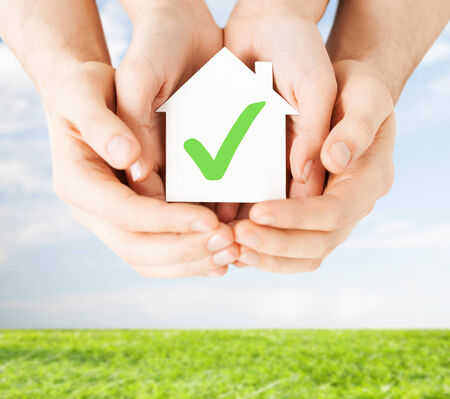 hands holding house: real estate and family home concept - male and female hands holding paper house with green check mark