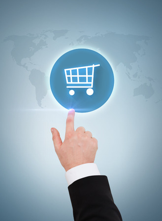 business, shopping and advertisement concept - close up of businessman pointing to shopping cart button photo