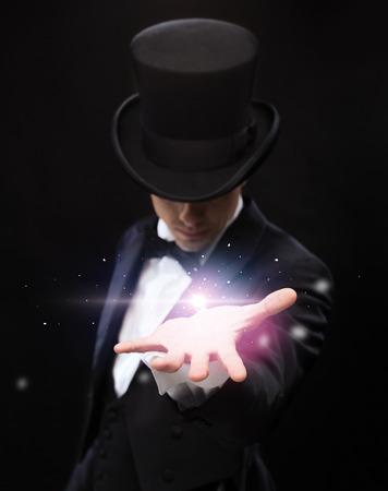 마술, 공연, 서커스, 표시 및 광고 개념 - 그의 손의 손바닥에 마술사 들고 뭔가 스톡 콘텐츠