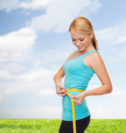 woman measuring waist: diet, sport and heath concept - beautiful sporty woman with measuring tape