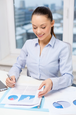 business, technology, internet and office concept - smiling businesswoman with laptop and charts in office photo