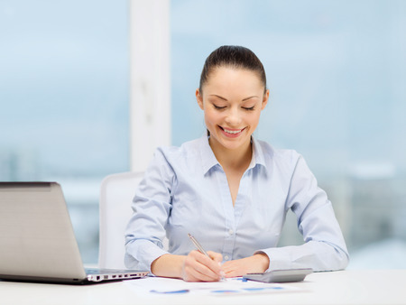 business, office and tax concept - smiling businesswoman working with documents in office photo