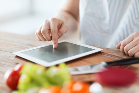 cooking, technology and home concept - closeup of man pointing finger to tablet pc computer photo
