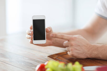 cooking, technology, advertising and home concept - close up of male hands holding smartphone with blank black screen photo