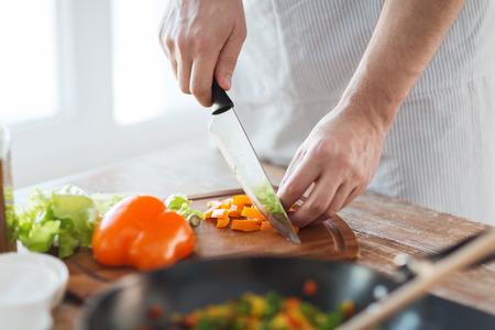 料理、食品、ホーム コンセプト - を自宅のまな板に男手切断唐辛子のクローズ アップ 写真素材
