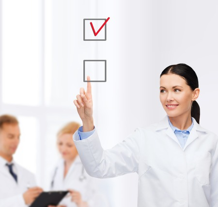 healthcare, medicine and technology concept - smiling female doctor pointing to checkbox photo