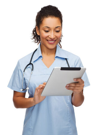 healthcare, technology and medicine concept - smiling female african american doctor or nurse with stethoscope and tablet pc computer photo