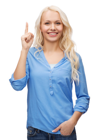 advertisement concept - attractive young woman in casual clothes pointing her finger up photo