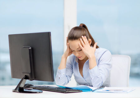 education concept: business, office, school and education concept - stressed businesswoman with computer and documents at work