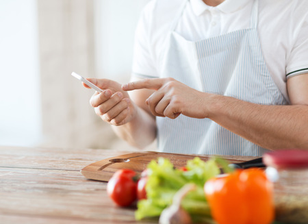 cooking, technology and home concept - closeup of man pointing finger to smartphone photo