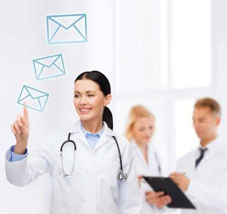 smiling female doctor with stethoscope pointing to envelope photo