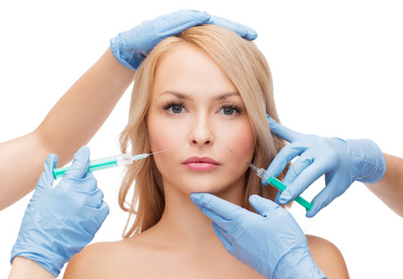 woman face and beautician hands with syringes photo