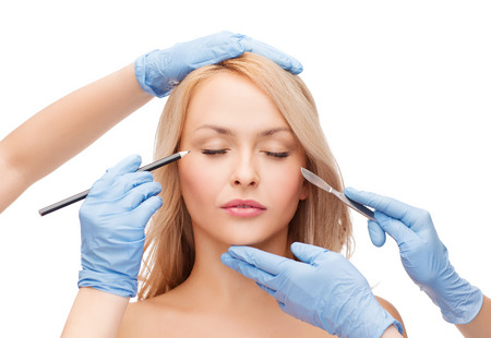 beautiful woman face with closed eyes and beautician hands with pencil and scalpel photo