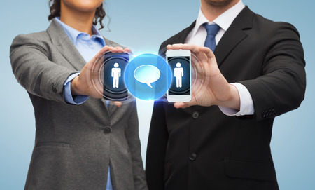 business, technology and internetconcept - businessman and businesswoman with social or business network on smartphone screens photo