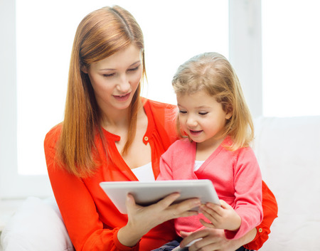 family, children, parenthood, technology and internet concept - happy mother and daughter with tablet pc computer at home photo