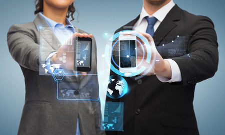 business, technology and internetconcept - businessman and businesswoman with chart and graphs on smartphone screens photo
