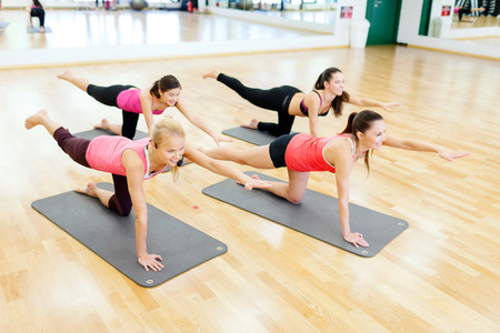 instructor: fitness, sport, training, gym and lifestyle concept - group of smiling women stretching on mats in the gym