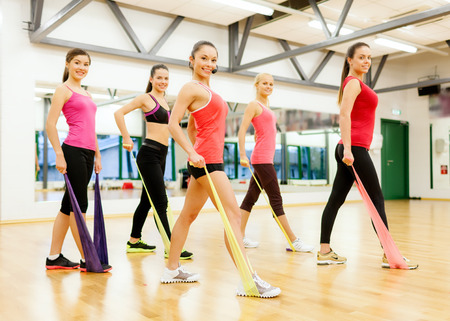 elastic: fitness, sport, training, gym and lifestyle concept - group of smiling people with instructor working out with rubber bands in the gym