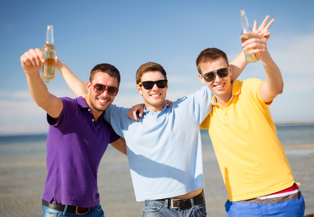 summer, holidays, vacation and people concept - group of male friends having fun on the beach with bottles of beer or non-alcoholic drinks photo